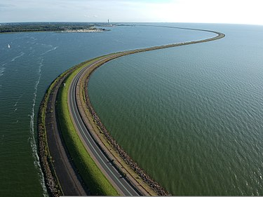 The Houtrib dam on the IJssel lake near Lelystad, Flevoland province. above view of dark blue water and the road on top of the dam.