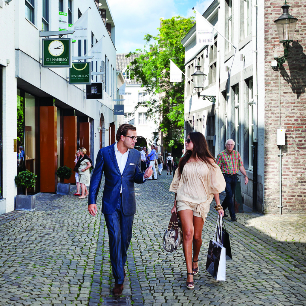 A designer outlet shopping village in Roermond. One of the streets is seen here, with the flags of the represented brands atop the stores. A man in a blue suit and a woman in a beige outfit are talking and shopping here.
