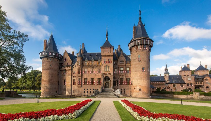A picture of De Haar castle in Haarzuilens, Holland. The statuesque castle has round towers, cone shaped roofs and many windows. The garden around the castle is well-kept. The green grass, red and white flowers, combined with the blue sky, make the castle stand out.