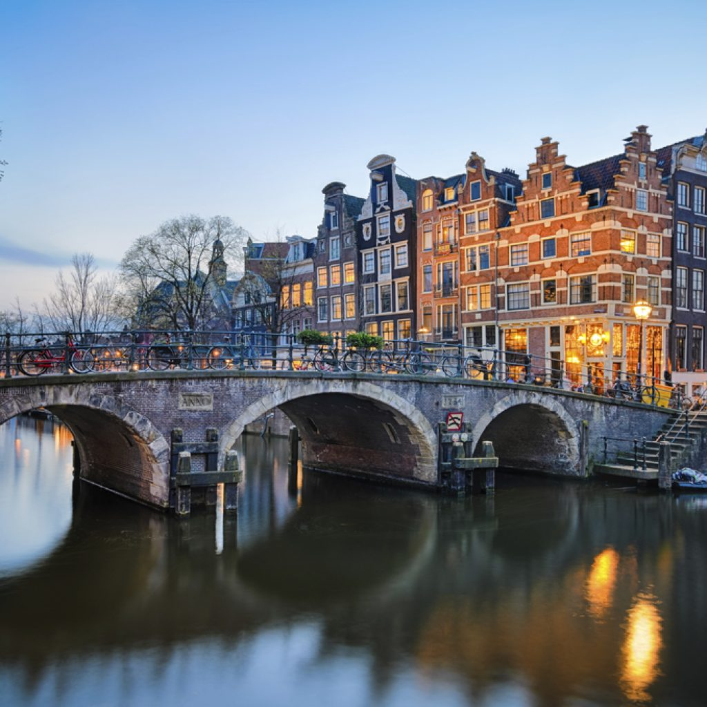 A view of the Amsterdam canal and canal houses at dusk. This location is a part of the Holland Highlights and Amsterdam tours.