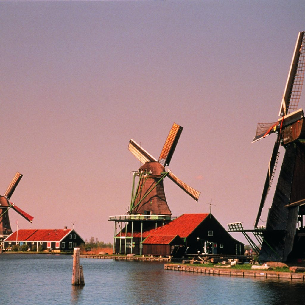 An outlook of windmills at Zaanse Schans. The blue water and the orange-blue sky make for a great photo opportunity. This location is a part of the Holland Highlights and Amsterdam tours.