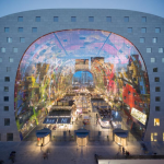 Rotterdam Markthal (Market Hall) by night. The vibrant colours of the roof are clearly visible here, as if the organic shape of the building itself. This location is a part of the Holland Highlights and Art and Architecture tours.
