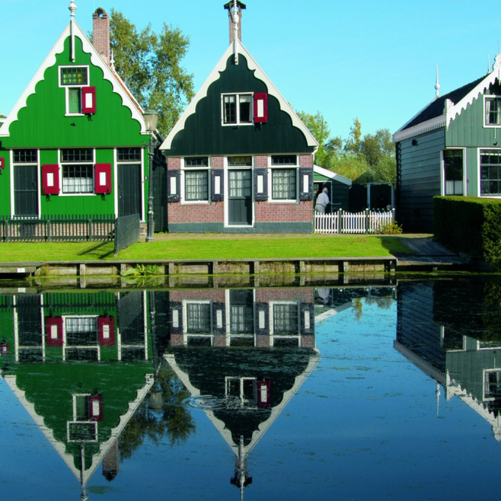 Old style Dutch houses at Zaanse Schans. The water is so clear the image of the houses is reflecting in the water. This location is a part of the Holland Highlights and Amsterdam tours.