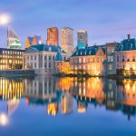 The Hague's main building of national government, called the Binnenhof. The picture is taken during nightfall and shows the clarity of the water and the vibrant lights coming from the building. This location is a part of the Holland Highlights tours.
