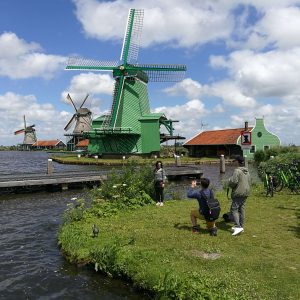 Tourists taking pictures of the famous Zaanse Schans view. This view includes blue skies, white clouds, green grass and even greener windmills.