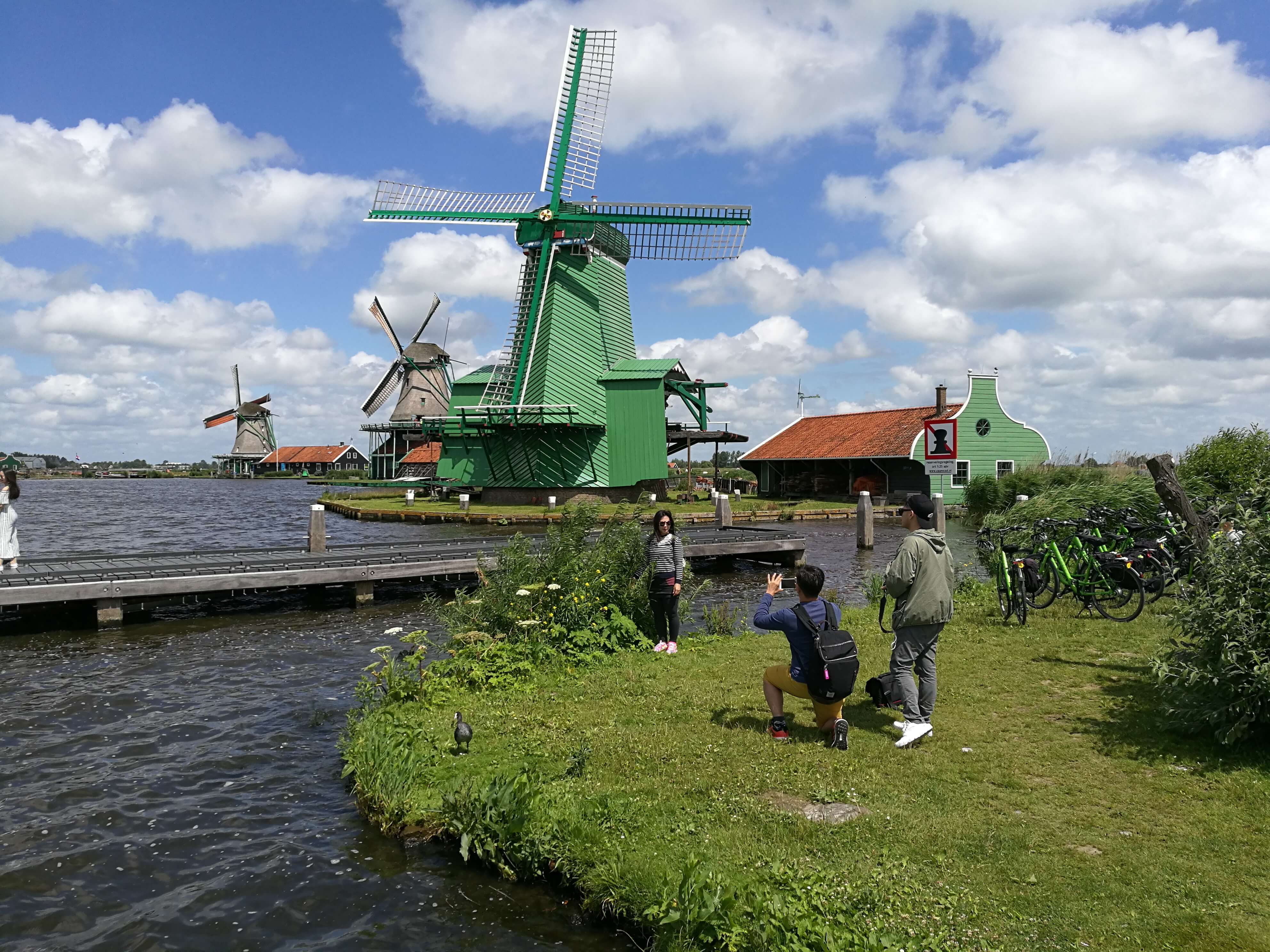 Tourists taking pictures of the famous Zaanse Schans view near Amsterdam.