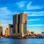 An example of the modern skyline of Rotterdam. The picture is taken from the water. The blue from the water and the sky seem to melt into one blue colour. The building is standing fierce in this field of blue.