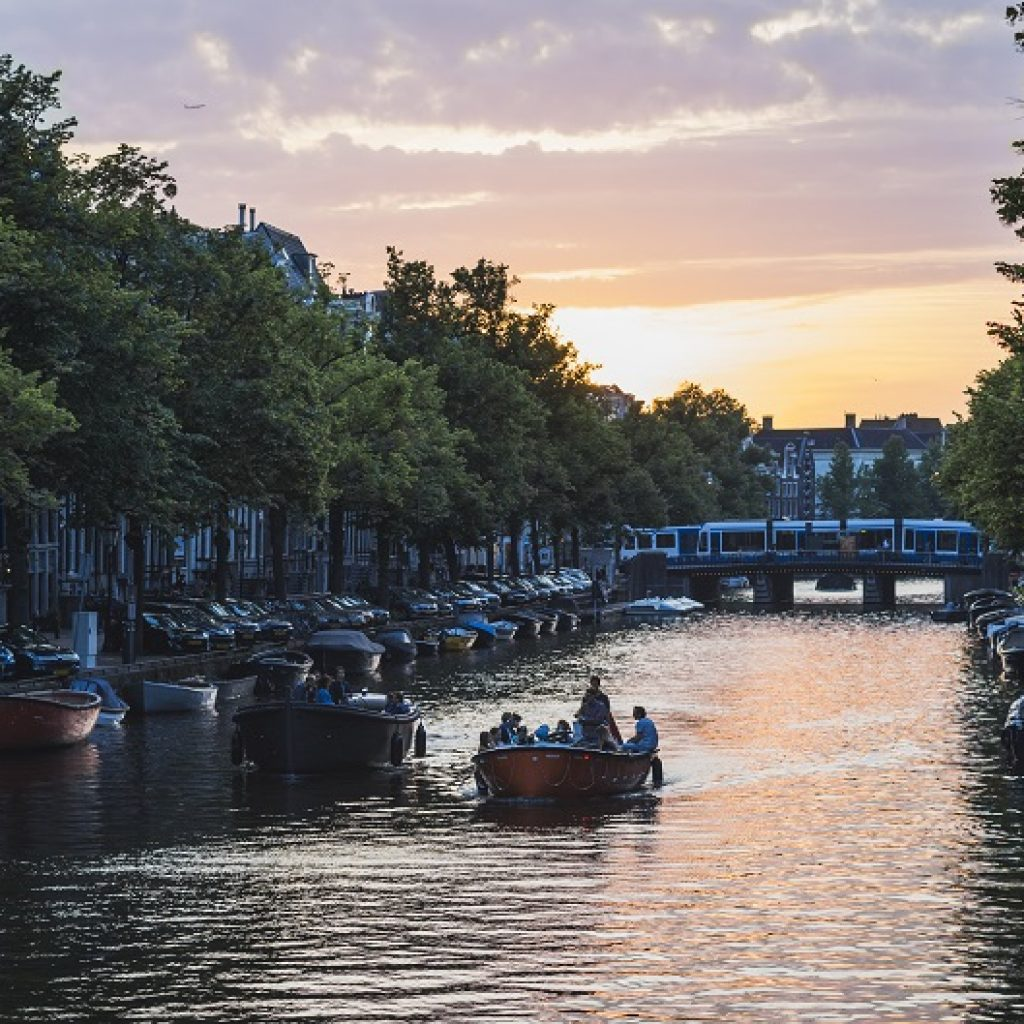 Amsterdam canal with trees and merchant houses, pink and lilac evening sky, boats on the water
